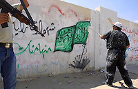 Guarded by armed policeman, a Palestinian Municipal worker paints over a Hamas flag outside the Islamic university in Gaza Strip, July 10, 2003. Municipal workers started to paint over graffiti in Gaza City. Photo by Quique Kierszenbaum.