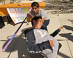 Adrian Barrera, 18, Carson City, reacts as Jovani Arroyo 10, makes it under the bar during a limbo contest during the 7th Annual Easter Fiesta at Western Nevada College Saturday, March 26, 2016. The event, hosted by the Association of Latin American Students, had 3 separate egg hunts, face painting, limbo, musical chairs, ring toss, sack races, bowling,  food, music and a piñata. Barrera is a member of the student association. <br />