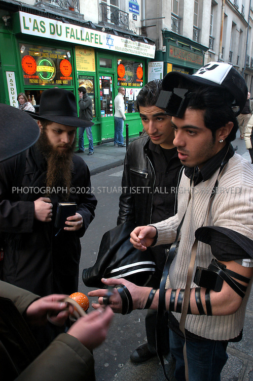 2/13/2004--Paris, France..Mordechai Kustiner (20, left with beard) helps a Jewish resident (no name given) of the Le Marais quarter in Paris put on the 'teffilin' for prayers on the eve of the Sabath, on Rue des Rosiers. Paris city officials want to close the street to make a pedestrian shopping area but local residents are affraid such a move would continue the comercialization of the neighborhood and the destruction of the city's old Jewish quarter and its way of life...Photograph by Stuart Isett/Polaris              .©2003 Stuart Isett. All rights reserved