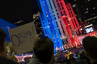 New York, NY - 4 November 2008 - Crowds gathered in Rockefeller Center, dubbed Election Square, to watch the 2008 Presidential Election results on giant flat panel television screens. Blue and Red ribbonsd on the fascade of 30 Rock illustrate the number of electoral votes for each candidate...Democrats wave Obama signs as NBC news announces he is the projected winner of the 2008 presidential election.