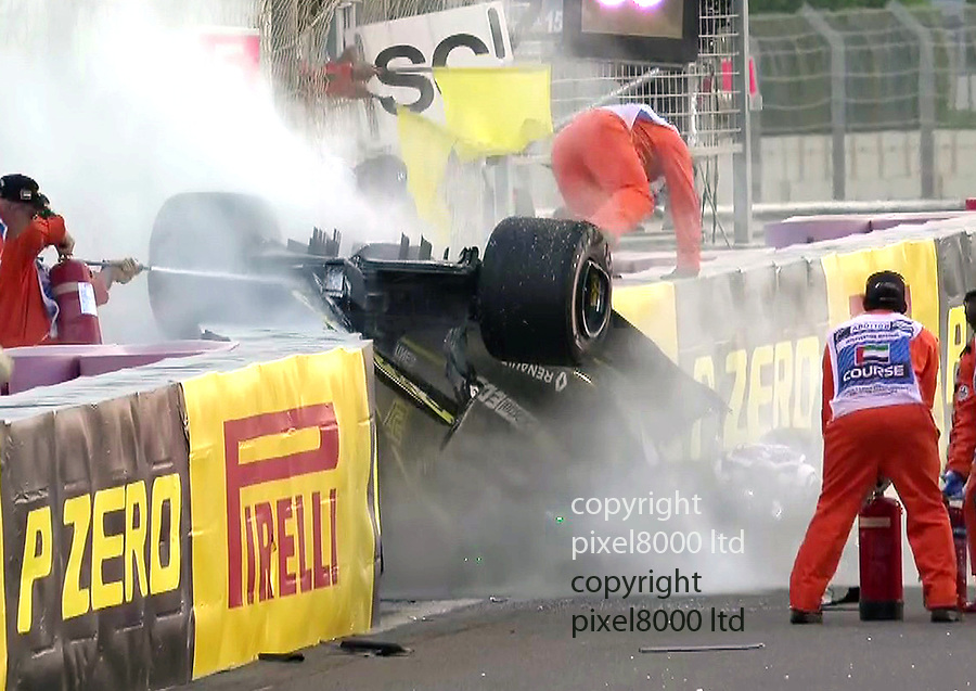 Pic shows: F1 Abu Dhabi<br /> <br /> Shocking crash by Nico Hulkenberg  on first lap<br /> <br /> Grosjean's left front hit Nico Hulkenberg's rear and flipped him round. <br /> <br /> <br /> Concern as he is trapped in the car which catches fire. But he's okay<br /> <br /> <br /> pic by Pixel8000 Ltd