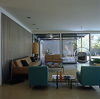 The living room, furnished with classic pieces of period 60s furniture, looks out onto the covered terrace