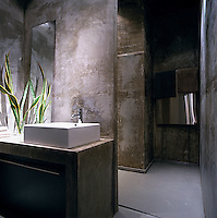The square wash basin sits on a concrete surface in this contemporary bathroom with walls painted in a distressed finish