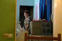 A woman laughs behind the counter of a cafe in Tbilisi...