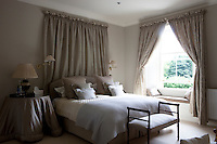 A comfortable bedroom decorated in shades of grey. The double bed has an upholstered headboard and a window seat provides a sunny spot to sit