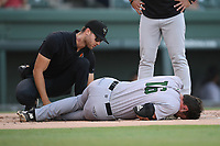 First baseman Logan Wyatt (16) of the Augusta GreenJackets is tended to after fouling a ball off his knee in a game against the Greenville Drive on Thursday, August 29, 2019, at Fluor Field at the West End in Greenville, South Carolina. He had to be removed from the game. Augusta won, 11-0. (Tom Priddy/Four Seam Images)