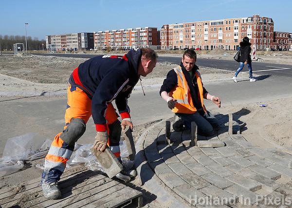 Stratenmakers aan het werk in een nieuwbouwwijk in Almere