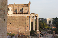 Temple of Antoninus and Faustina, 141 AD, transformed in the Christian era into the church of San Lorenzo In Miranda remaining the façade with the colossal columns in Euboeian marble, Arch of Titus (70 AD) in the distance, Roman Forum, Rome, Italy, Europe.