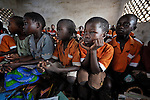 "Gota Dzongololo (hands on chin), 11, listens to the teacher in a primary school class in Chidyamanga, a village in southern Malawi that has been hard hit by drought in recent years, leading to chronic food insecurity, especially during the ""hunger season,"" when farmers are waiting for the harvest."