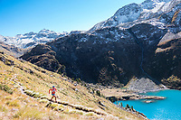 Running above Lac de Cleuson during the Via Valais, a multi-day trail running tour connecting Verbier with Zermatt, Switzerland, with fresh snow on the mountains.