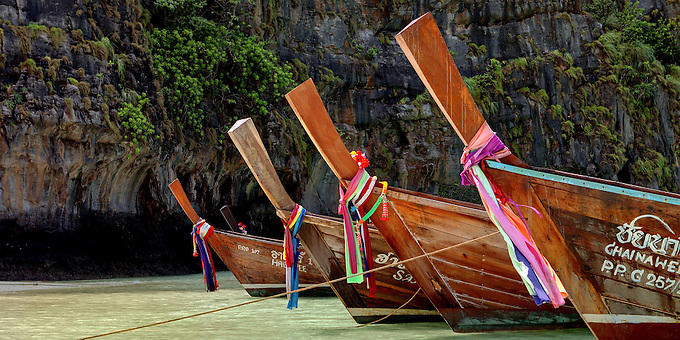 Long tail boats rest in the emerald waters of Maya Bay.