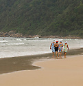 Old Women walking down the beach in Guaruja, Brazil
