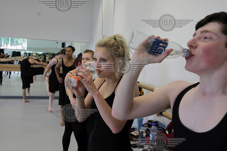 Students take on fluids during a break in a dance class at the Brit School, in Croydon. The Brit is Britain's only non-fee paying performing arts and technology school.