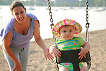 mom pushes her cute baby girl on a swing in summer on a city beach, Lake Calhoun, Minneapolis, Minnesota