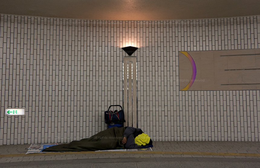 A homeless Brazilian-Japanese immigrant sleeps in Hamamatsu Station. Hamamatsu, Shizuoka, Japan. Sunday, March 22nd 2009