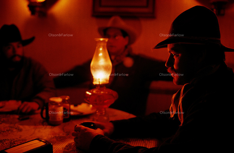 Cowboys share morning coffee by lantern while preparing for a roundup on the ranch.