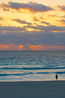 Man standing on a beach watching morning sunrays break through the clouds (portrait)