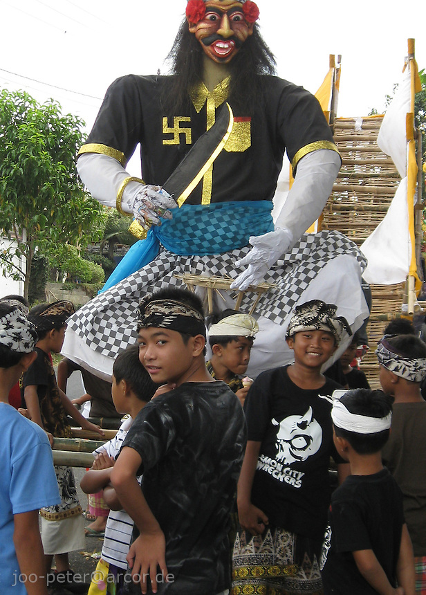 kids have fun to carry a protective demon while cremation ceremonies, to keep off lower demons, cremation in Bangli, central Bali, archipelago Indonesia, 2009