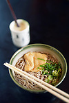 Bowl of Ramen with Soba noodles and tofu and Amazake drink on a table in a Japanese restaurant, Kyoto, Japan.