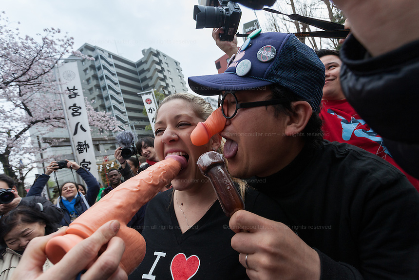 Tourist joke with a dildo and penis shaped lollipops during the Kanamara Matsuri, (Festival of the Steel Phallus). Kawasaki Daishi, Kanagawa, Japan. Sunday April 3rd 2016. The famous Kawasaki Penis Festival started in 1977 as a small festival to celebrate an old legend about the defeat of a penis eating demon. Today the festival is a huge draw for Japanese and foreign tourists and raises money for HIV and AIDS research.