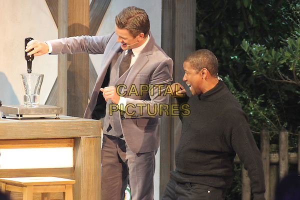 "show host Markus Lanz & Denzel Washington.Germany's biggest live TV-show ""Wetten Dass"", Offenburg, Germany..January 19th, 2013.half length black top sweater jumper beige grey gray suit side profile hand arm liquid pour pouring water funny bottle.CAP/UNT.©Unit2/Capital Pictures"