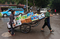 Daytime landscape view of a man and a woman pulling a hand cart loaded with fruit boxes on Hui Long Jie in Lóngmǎtán Qū of the Lúzhōu Prefecture City in Sichuan Province.  © LAN