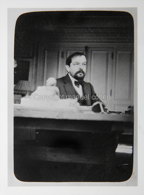 Portrait of Claude Debussy, 1862-1918, French composer, at his desk in his home at 80 Avenue du Bois de Boulogne, Paris, France, photograph. Copyright © Collection Particuliere Tropmi / Manuel Cohen
