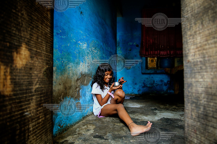 A young girl eats a meal while sitting in the doorway of her home.