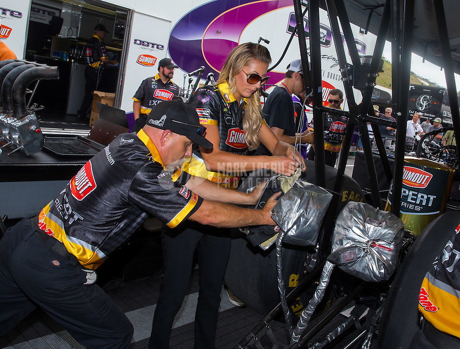Jun 19, 2015; Bristol, TN, USA; A crew member helps NHRA top fuel driver Leah Pritchett pack her parachute during qualifying for the Thunder Valley Nationals at Bristol Dragway. Mandatory Credit: Mark J. Rebilas-