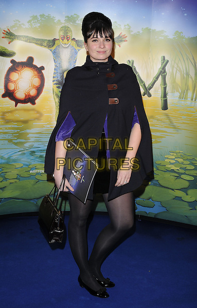 "GIZZI ERSKINE.At the Cirque du Soleil ""Totem"" press Tour, Royal Albert Hall, Kensignton Gore, London, 5th January 2011..full length black cap poncho coat buckles tights purple bag .CAP/CAN.©Can Nguyen/Capital Pictures."