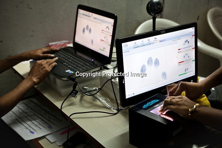 An official assists a villager while he places his fingers for fingerprint scan during the enrollment process in Naagaaram village, outskirts of Hyderabad in Andhra Pradesh, India. India is assigning each one of its 1.2 billion people a unique ID number based on digital finger prints and iris scan. Photograph: Sanjit Das/Panos