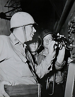 Chaplin P.H. Martineau prays through the ships intercom in the morning to officers and crew during G.Q.. Assiting him are bugler F.J. Pursely and coxswain J.J. Allen.   -  Aug. 3, 1945