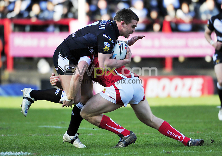 PICTURE BY VAUGHN RIDLEY/SWPIX.COM - Rugby League - Super League - Salford v Hull FC - The Willows, Salford, England  - 27/03/10...Copyright - Simon Wilkinson - 07811267706...Hull FC's Shaun Berrigan is tackled by Salford's Malcolm Alker.