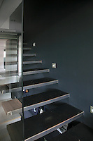 The black-painted wall along one side of the cantilevered steel staircase creates a stunning contrast to the transparent glass wall on the opposite side