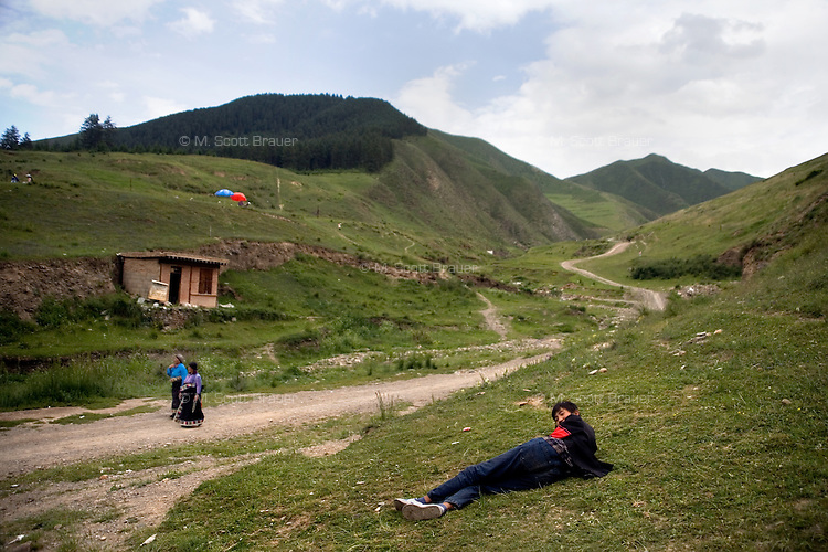 Tibetan Buddhist pilgrims rest on a hillside outside the Labrang monastery grounds in Xiahe, Gansu, China. Xiahe, home of the Labrang Monastery, is an important site for Tibetan Buddhists.  The population of the town is divided between ethnic Tibetans, Muslims, and Han Chinese.