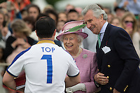 Her Majesty the Queen and Arnaud M. Bamberger (Executive Chairman) present Aiyawatt Srivaddhanaprabha (King Power Foxes) with the Winning awards during the Cartier Queens Cup Final match between King Power Foxes and Dubai Polo Team at the Guards Polo Club, Smith's Lawn, Windsor, England on 14 June 2015. Photo by Andy Rowland.