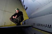 A plane captain on the tail of his aircraft in the hangar bay aboard USS Abraham Lincoln.