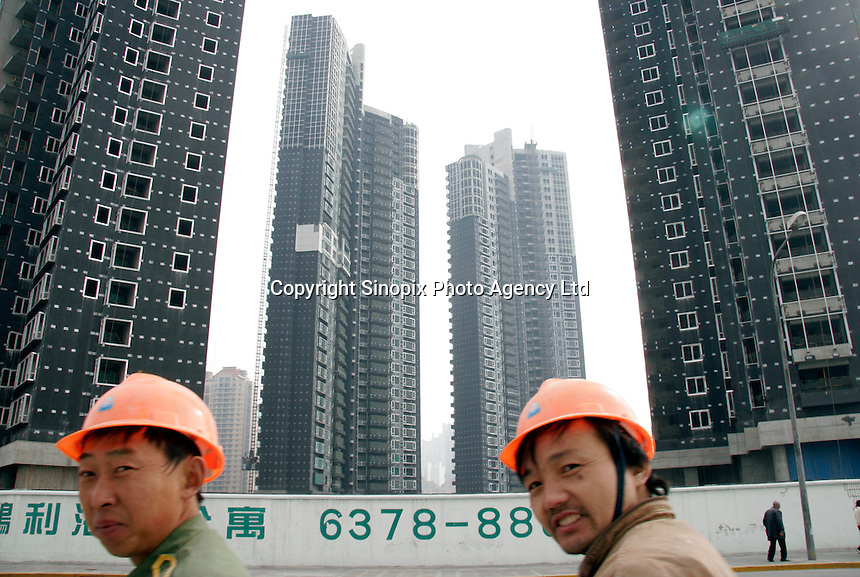 Construction workers walk through an intersection filled with new apartment high rises in Shanghai, China. The Shanghai government announced recently that it will no longer consider real estate as one of the city's key sectors due to Beijing macro-economic control policies for the 11th five-year plan, instead the city will focus development in aviation and marine-related industries..