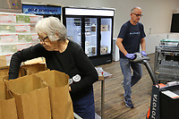 Kathy Kingsbury (left), a volunteer at FEED the 479 food pantry at the Compassion Center, packs United States Department of Agriculture food bags for distribution at the center in Springdale. FEED the 479 is changing to a drive through method to pick up food items. The food can be picked up on Monday and Thursday from 9:30 a.m. to 11:30 a.m. and Tuesday and Wednesday from 5:00 p.m. to 7:00 p.m.. Check out nwaonline.com/200319Daily/ and nwadg.com/photos for a photo gallery.<br /> (NWA Democrat-Gazette/David Gottschalk)