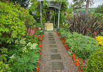 Vashon-Maury Island, WA: Garden path lined iwth impatiens leads to a small romantic table under a pergola covered in wisteria. Perennials include multi-colored astilbes, euphorbia and phormium