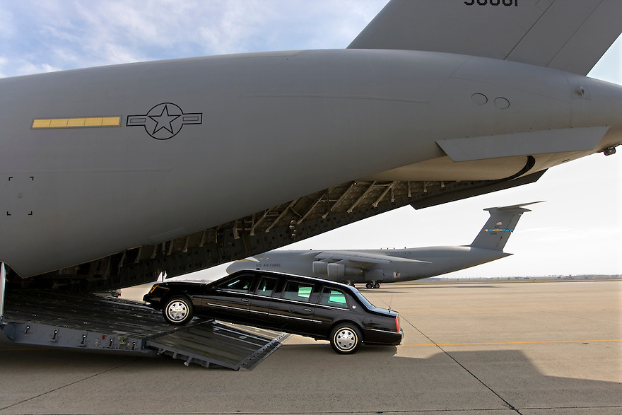 "A Presidential limousine is loaded onto a C5 military transport plane bound for eastern Europe, where President Bush is headed next week.  A ""secure package"" of motorcade vehicles, including the limousines and a fleet of Secret Service SUVs is transported to the site of every presidential visit. ..Photo by Brooks Kraft/Corbis........."