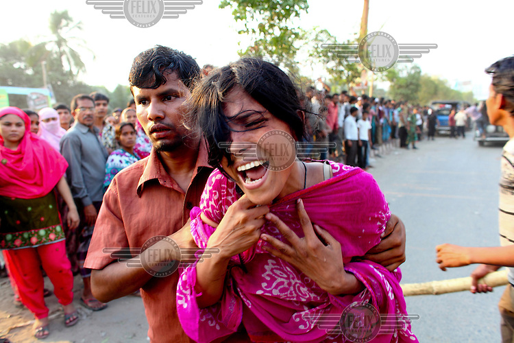 A woman cries while held by a man in front of the collapsed Rana Plaza complex in Savar. A large crowd of onlookers gathers in front of the collapsed Rana Plaza complex in Savar. The 8 storey building, which housed a number of garment factories employing over 3,000 workers, collapsed on 24 April 2013. By 29 April, at least 380 were known to have died while hundreds remained missing. Workers who were worried about going to work in the building when they noticed cracks in the walls were told not to worry by the building's owner, Mohammed Sohel Rana, who is a member of the ruling Awami League's youth front. He fled his home and tried to escape to neighbouring India after the building collapsed but was caught by police and brought back to Dhaka. Some of the factories working in the Rana Plaza building produce cheap clothes for various European retailers including Primark in the UK and Mango, a Spanish label. . /Felix Features