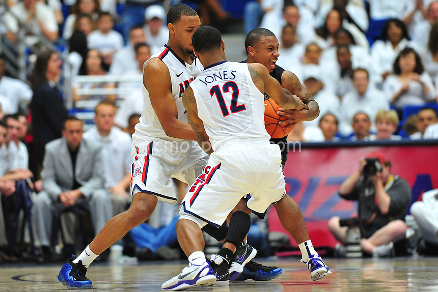 Feb 19, 2011; Tucson, AZ, USA; Washington Huskies guard Isaiah Thomas (2) gets double-teamed by Arizona Wildcats guard Lamont Jones (12) and forward Derrick Williams (23) in the 1st half of a game at the McKale Center.