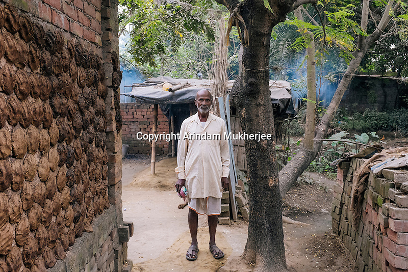 Anil Mondol stands in front his house on a Government land. Once the owner of more than 15 acres of land, he had to move to Ballalpur village on PWD land with his family in the year 2000 after all of his land and home was eaten away by the Ganges river. Currently he does not have any asset to his own name. Any day the Government can eradicate them from this land as by law they are illegal settlers. Ballalpur Village, Murshidabad, West Bengal. India.