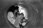 Girls make up in the abandoned concrete tube for construction in a park in Matsumoto, Nagao.