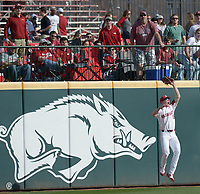 NWA Democrat-Gazette/ANDY SHUPE<br />Arkansas left fielder Heston Kjerstad leaps to catch a ball hit by Kent State catcher Tim Dalporto Friday, March 9, 2018, during the second inning at Baum Stadium in Fayetteville. Visit nwadg.com/photos to see more photographs from the game.