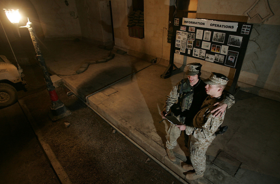 Corporals Jeromy Nelson (l.) and Benjamin Hilliard sing carols outside the headquarters for 2nd Battalion 5th Marines at the battalion's base - Hurricane Point - in Ramadi, Iraq on Christmas Eve December 24, 2004.