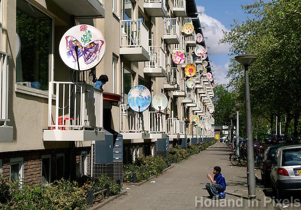 Straatbeeld met flat in Amsterdam-West. Schotels op balkons in een achterstandswijk