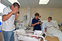 New born baby who has just been delivered by water birth. The infant has had a clamp placed on his umbilical cord. The midwife is performing the apgar score on the infant. This image may only be used to portray the subject in a positive manner..©shoutpictures.com..john@shoutpictures.com