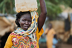 A woman carries water in Bunj, the host community for the Doro Refugee Camp in Maban County, South Sudan. Doro is one of four camps in Maban that together shelter more than 130,000 refugees from the Blue Nile region of Sudan. Jesuit Refugee Service provides educational and psycho-social services to both refugees and the host community.<br /> <br /> Misean Cara supports the work of JRS in the Maban camps and host community.